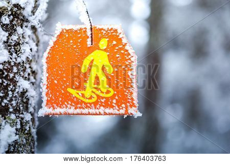 Snowshoeing hiking sign marker in trail snowy forest.
