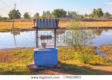 rural scene with water well on the river shore