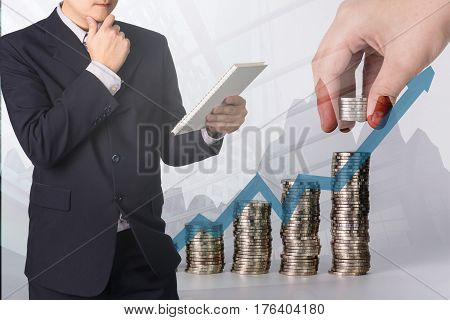 Double exposure Confident Asian businessman reading notebook or document file and thinking with financial growth graph chart on blurred stacks of coins with calculator background Money Financial Business Growth and saving money concept.