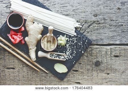 traditional asian ingredients ginger root pickled ginger dried ginger black and white sesame seeds udon noodles soy sauce on a stone plate on the old wooden background blank space for text toning
