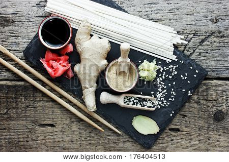 Traditional asian ingredients ginger root pickled ginger dried ginger black and white sesame seeds udon noodles soy sauce on a stone plate on the old wooden background top view