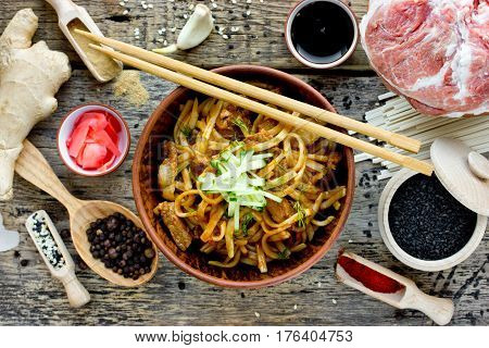 Chinese spicy dish udon noodles with meat sauce and vegetables top view