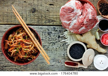 Wheat udon noodles with fried pork meat and sauce prepared dish and ingredients for cooking recipe of traditional Asian cuisine top view