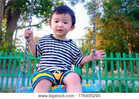 Young Asian Boy Play A Iron Swinging At The Playground Under The Sunlight In Summer.