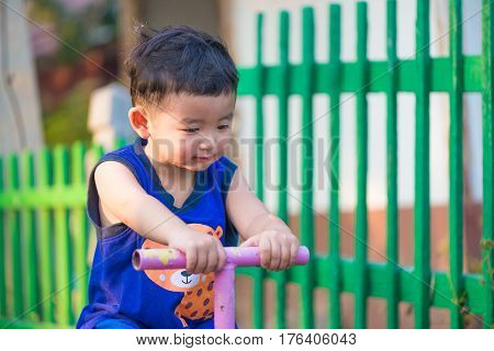 Asian Kid Riding Seesaw Board At The Playground.