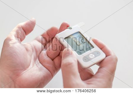 Medicine, Diabetes, Glycemia, Health Care And People Concept - Close Up Of Man Hands Testing High Bl