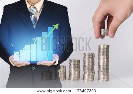 Double Exposure Of Growth Graph On Businessman Hand With Blurred Hand Put Coin In Stacks Of Coins Ba