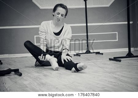 Pretty Young Graceful Ballet Dancer Warms Up In Ballet Class. Tired And Pain Of Hard Training