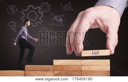 Business, Technology, Internet And Network Concept. Young Businessman Shows The Word: Llc