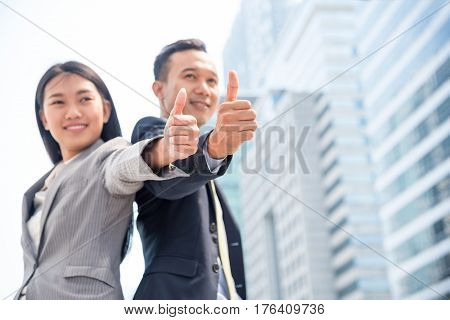 Cheerful young businessman and businesswoman giving thumbs up sigh with the background of urban landscape. Successful business concept. Copy space.