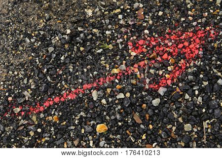 Red arrow on the ground in black gravel