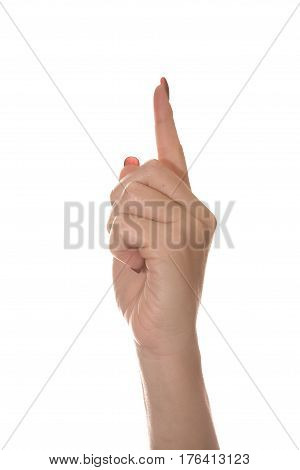 The index finger of the hand is raised up. Beautiful and graceful female hand on a white background shows different gestures.