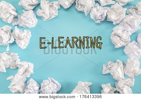 E-Learning text with crumpled paper balls on a blue background