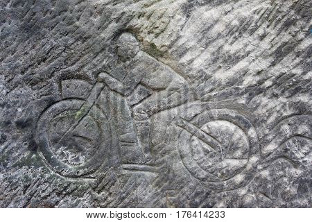 Racer on a motorbike - old rock relief Czechia