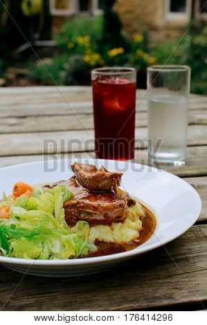 Lamb shank with vegetables on an pub outdoor wooden table, glass of water and juice next to it