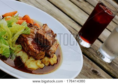 Lamb shank with vegetables on an pub outdoor wooden table