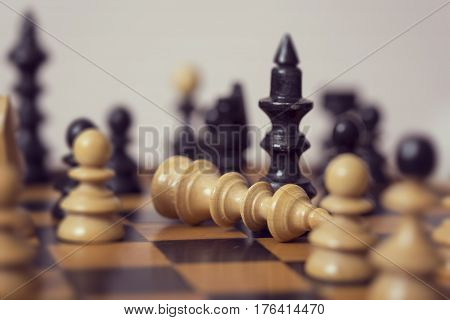 Close up of a wooden chess board and pieces black queen has beaten a white king. Selective focus