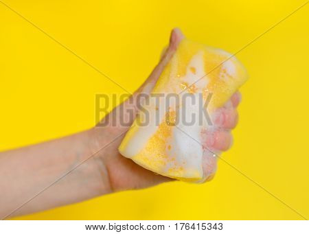 Hand with sponge with foam on yellow background