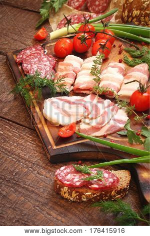 Delicatessen smoked meat bacon vegetables tomatoes parsley on a wooden boards
