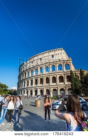 Girls outside Colosseum Rome. Rome, Italy - April 20, 2015: Tourists outside Colosseum, Rome. Five girls in the foreground taking pictures and talking, Colosseum and other tourists in the background.
