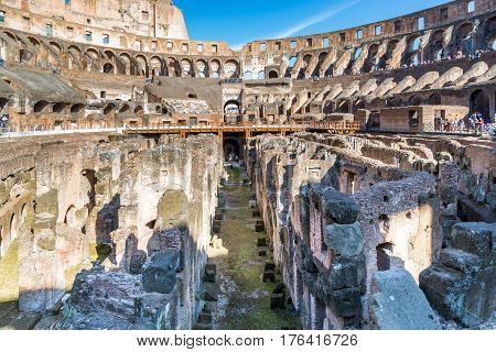 Low view of inside Colosseum, Rome. Rome, Italy - April 22, 2015: Low angle view of inside Colosseum in Rome to show ancient floor and tunnel construction.  Tourists seen in the background.