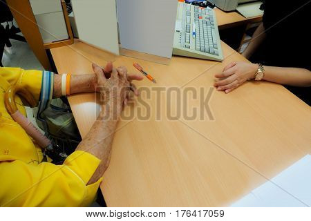 Grandma contacted and open an new account or buy a bank fund with female employees with key bord photo crop only hand on wood desk Leaflet computer retouch for copy space.