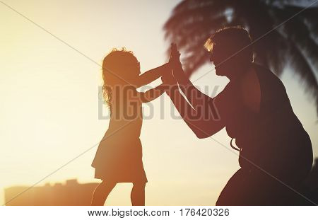 silhouette of grandmother and little granddaughter play at sunset beach