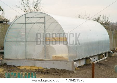 Greenhouse made of polycarbonate outside in the early spring. Three beds.