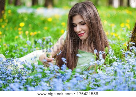 Young woman is lying on field with forget-me-not