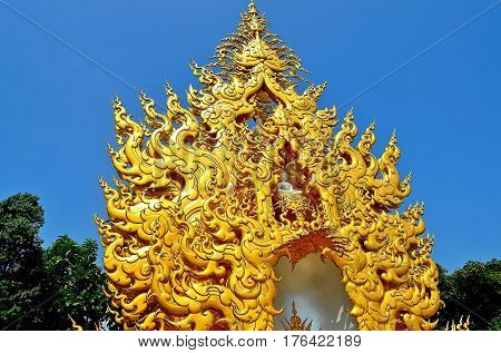 The white Buddha in the golden crown blissfully looks into the world