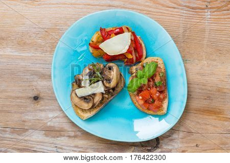 Bruschetta with tomatoes mushrooms goat's cheese background