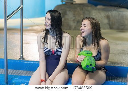 Young woman sits on pool in aqua park