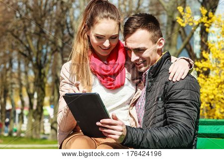 Modern technologies leisure and relationships concept. Young couple with pc computer tablet sitting on bench outdoor websurfing on internet