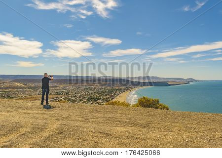 Man Taking Photos At Top Of Hill