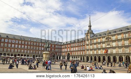 MADRID SPAIN - APRIL 22 2012: Tourists visiting Plaza Mayor in Madrid Spain. The Plaza Mayor (English Main Square) is a central plaza in the city of Madrid. It is located only a few Spanish blocks away from another famous plaza the Puerta del Sol.
