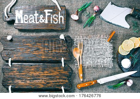 Dark wood boards as frames on burlap background with cutting tools, onions, lemon and salt. Wooden signboard with text 'Meat and fish' as title bar. Rustic style template for food and drink industry