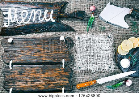 Dark wood boards as frames on burlap background with cutting tools, onions, lemon and salt. Wooden signboard with text 'Menu' as title bar. Rustic style template for food and drink industry