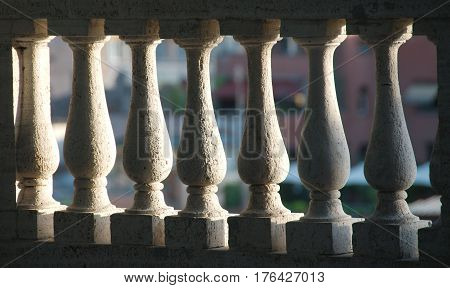 Detail of white stone balusters sunlit from one side