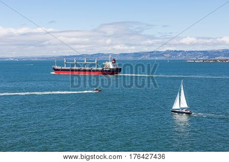 A massive freighter and small sailboat in the bay of San Francisco