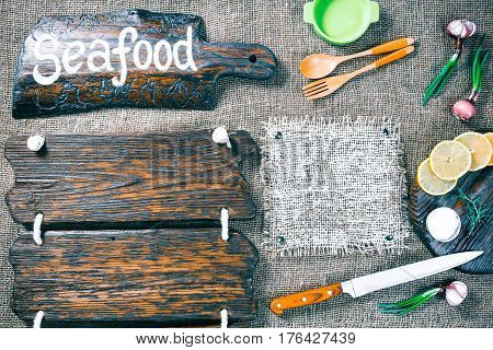 Dark wood boards as frames on burlap background with cutting tools, onions, lemon and salt. Wooden signboard with text 'Seafood' as title bar. Rustic style template for food and drink industry