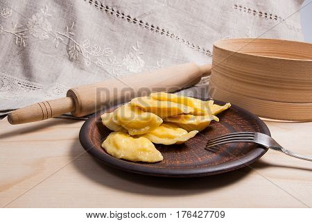 Fresh Boiled Varenyky Or Dumpling With Cottage Cheese Or Curd On Clay Plate And Metal Fork On Wooden