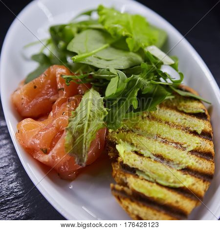 sandwich with smoked salmon, cheese, tomatoes and herbs for healthy breakfast. close up.