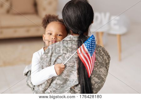 Glad to have you here. Lovely charming pretty girl hugging her mom tightly while greeting her home and holding a flag in her hand