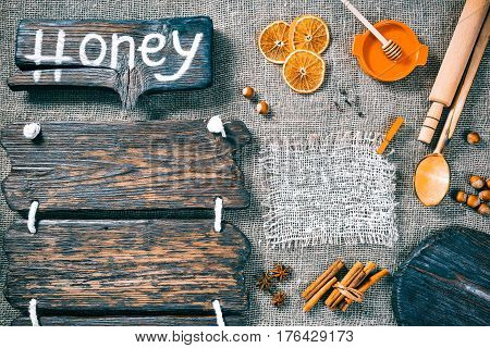Dark wood boards as frames on burlap background with honey, nuts and aromatic spices. Wooden signboard with text 'Honey' as title bar. Rustic style template for food and drink industry