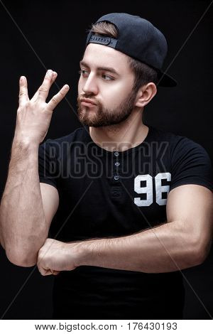 portrait of a handsome young brunette man in a black shirt and cap on a black background. rapper