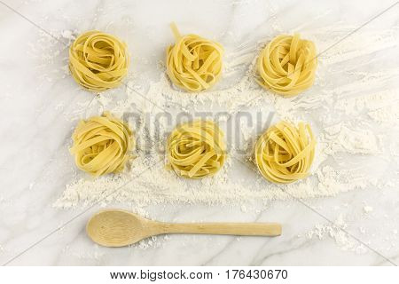 An overhead photo of pasta nests on a white marble table with flour and a wooden ladle