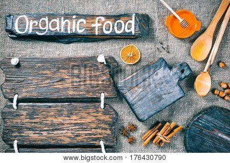 Dark wood boards as frames on burlap background with honey, nuts and aromatic spices. Wooden signboard with text 'Organic food' as title bar. Rustic style template for food and drink industry