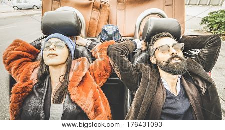 Fashion hipster boyfriend and girlfriend - Happy couple relaxing together at car trip - Modern love relationship concept with young people traveling together on the road - Vintage retro filter