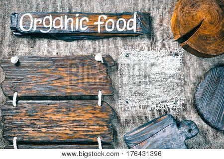 Dark wood boards, wood slice and burlap pieces as frames on burlap background. Wooden signboard with text 'Organic food' as title bar. Rustic style template for food and drink industry
