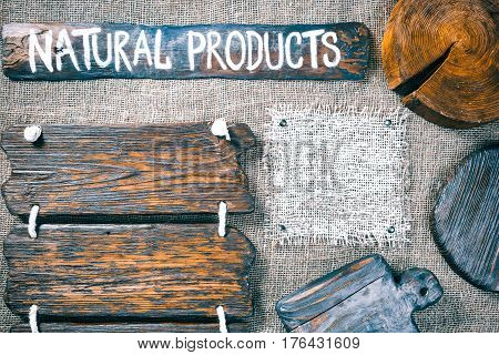 Dark wood boards, wood slice and burlap pieces as frames on burlap background. Wooden signboard with text 'Natural products' as title bar. Rustic style template for food and drink industry